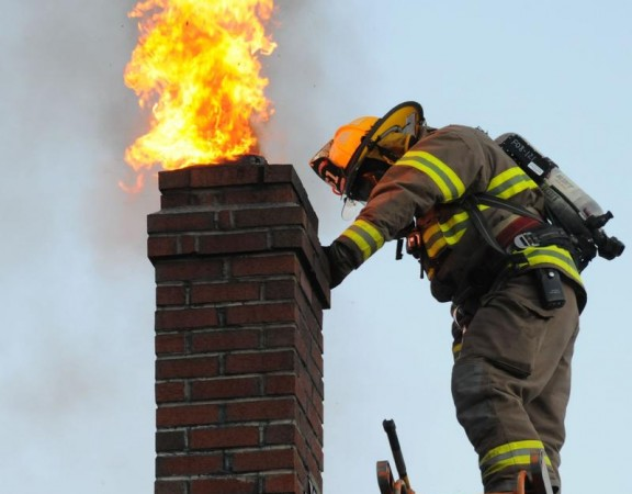 Freeport firefighter Jason Miller reacts as flames shoot out the chimney of a Brown Road home in Pownal on Saturday, where firefighters from Pownal and Freeport responded to a chimney fire. Miller and Lt. Ken Coslet attacked the problem from the roof, using a weight and chain to clear the chimney of material that had built up, but not before flames erupted several times. No damage was done to the 19th century home, a fortunate reminder to homeowners who burn wood to be diligent about keeping chimneys clean and using only seasoned firewood.